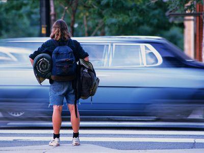 Homeless teenage girl on street corner with belongings