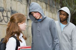 Teenage boys intimidating a teenage girl
