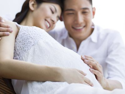 Pregnant woman with partner's hand on her belly