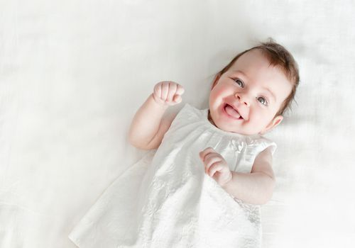 Baby girl in white dress on a white background.