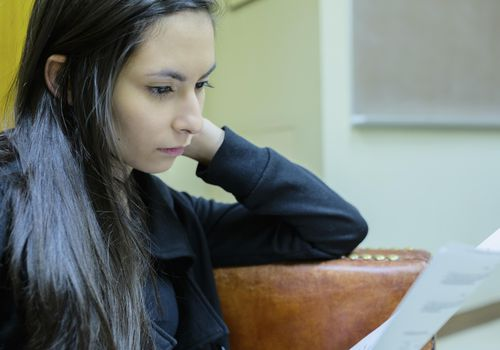 Young woman looking at a college rejection letter