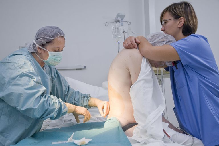 Nurse holds a laboring woman during epidural procedure