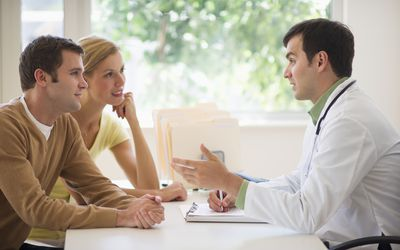USA, New Jersey, Jersey City, Couple receiving advice from doctor in office