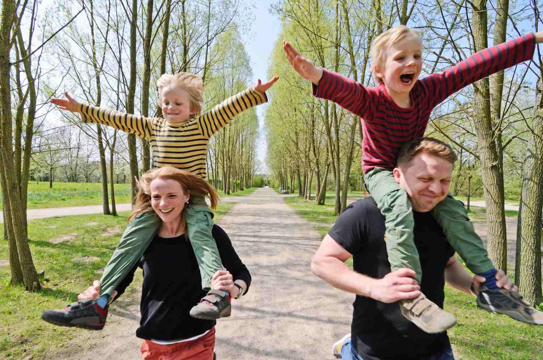Twins riding on parents' shoulders