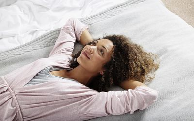 Woman relaxing on bed after sex
