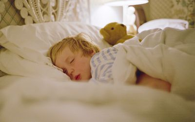 young boy asleep in a bed with a teddy bear