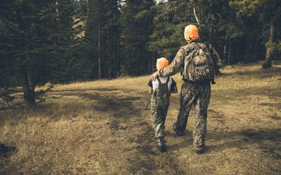 Grandfather and grandson hunters in camouflage bonding, walking in woods