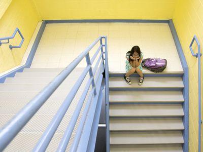 Bullied girl sitting on steps at school