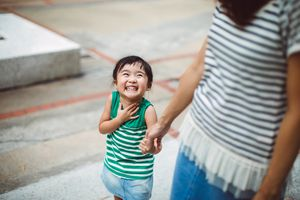 Smiling toddler holding hands with mom in park