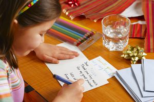 Girl (6-7) writing Thank You card, smiling