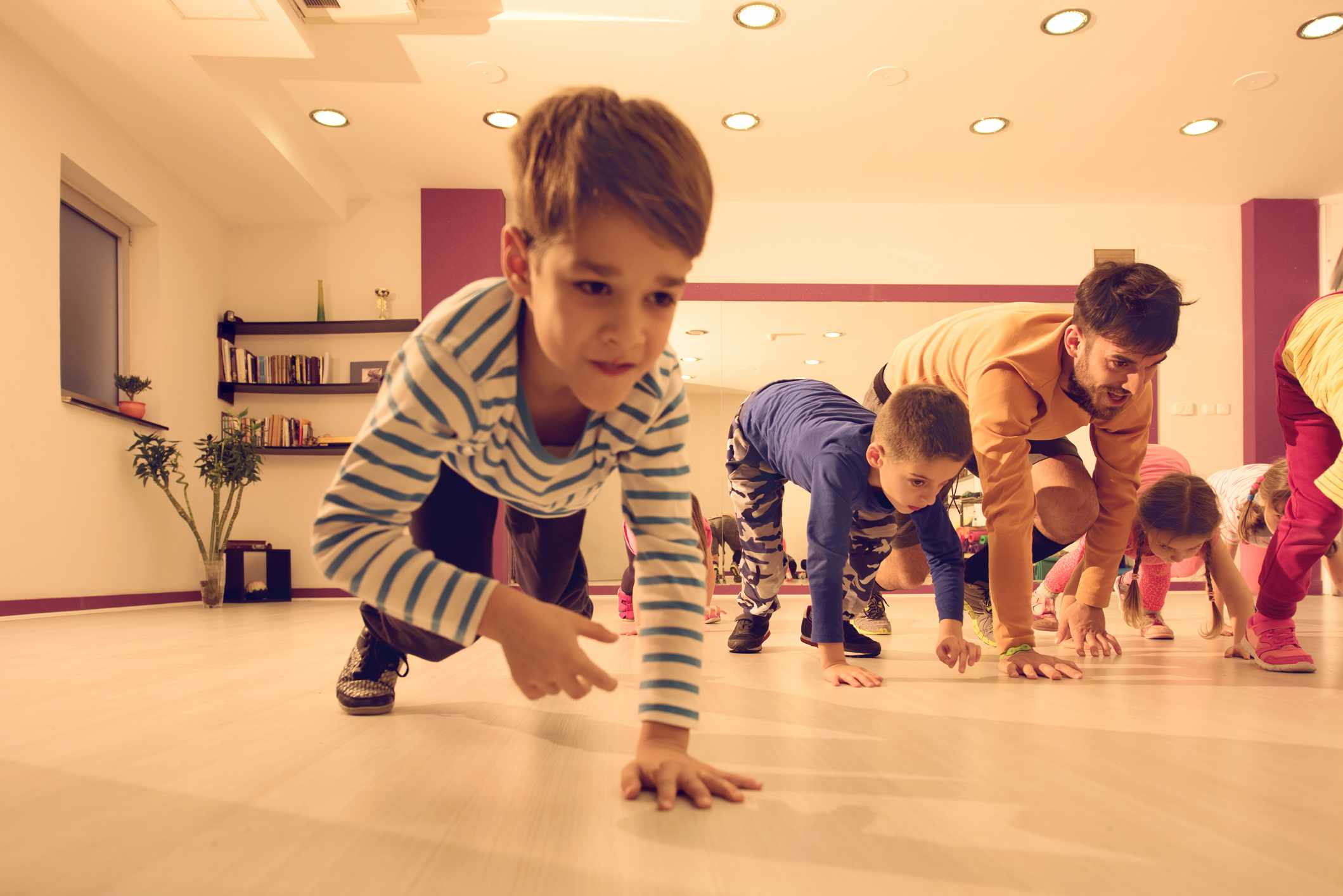 Children and dad doing bear crawl race