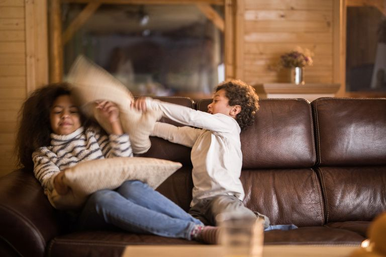 siblings having fun during a pillow fight at home.