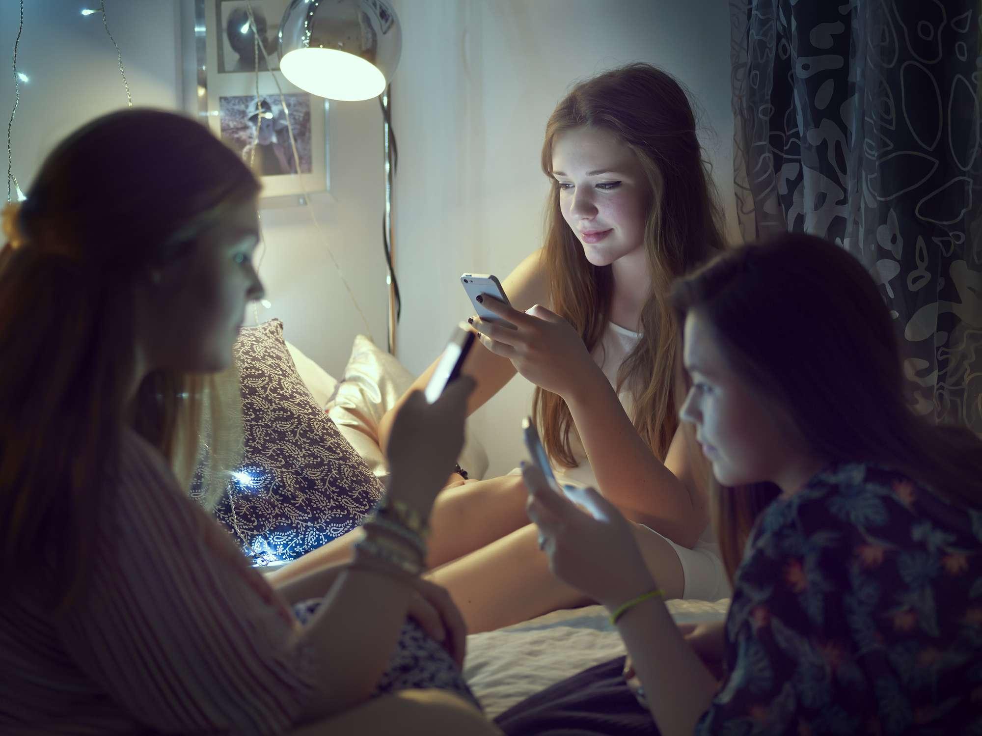 Three teen girlfriends using their smartphones