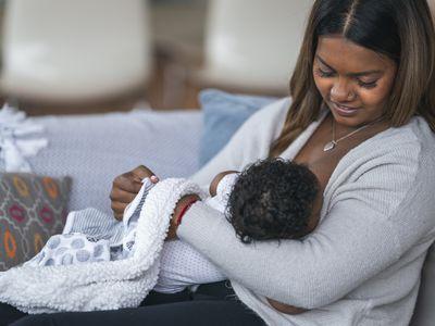 Woman nursing baby at home