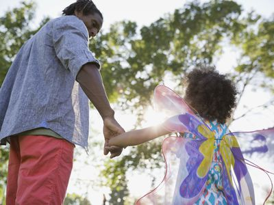 Father holding daughter's hand at the park