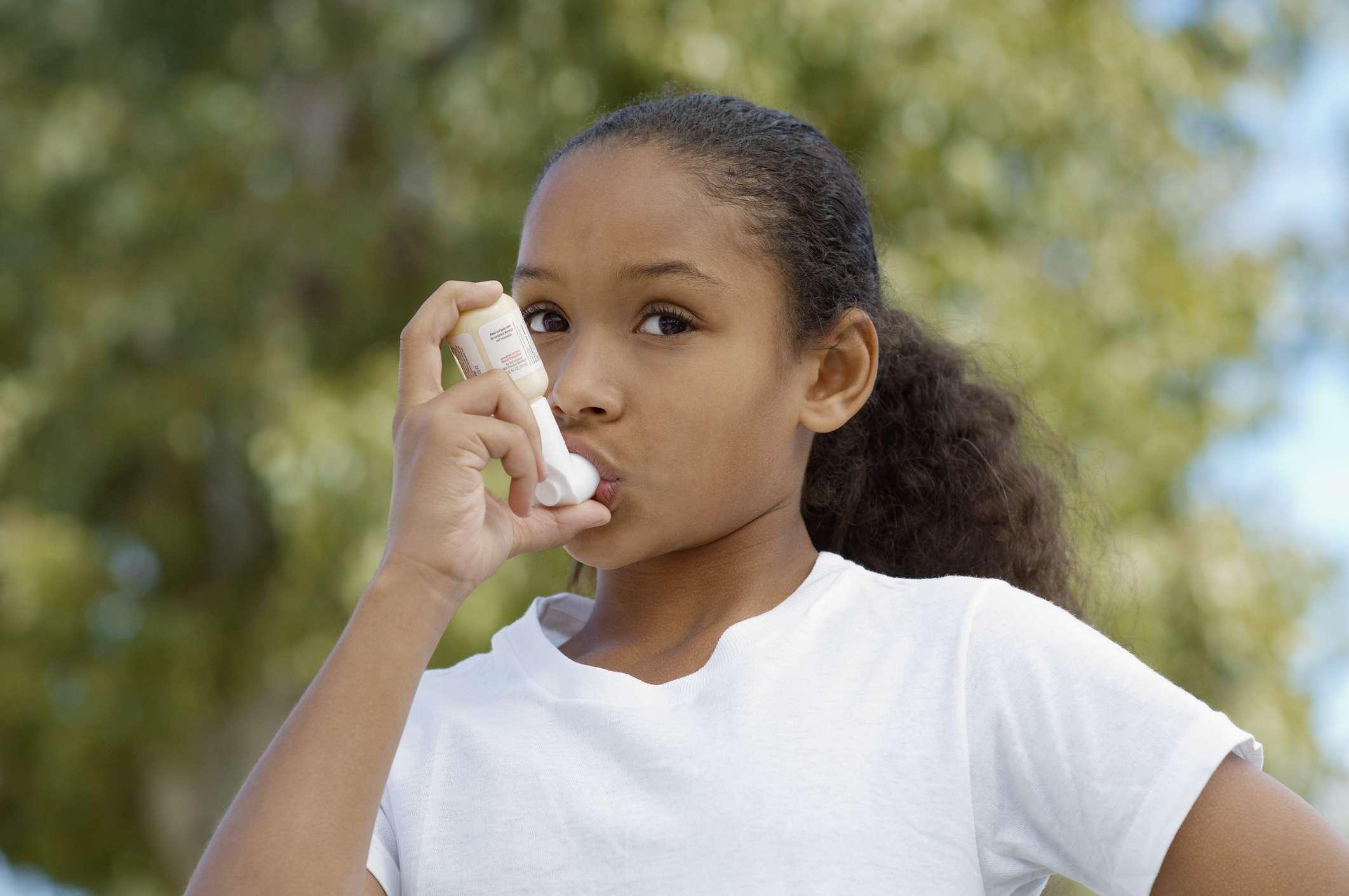 young girl using asthma inhaler