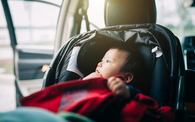 Portrait Of Curious Baby Sitting On Car Seat Looking Out From Window