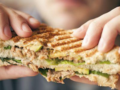 Hands holding a tuna sandwich