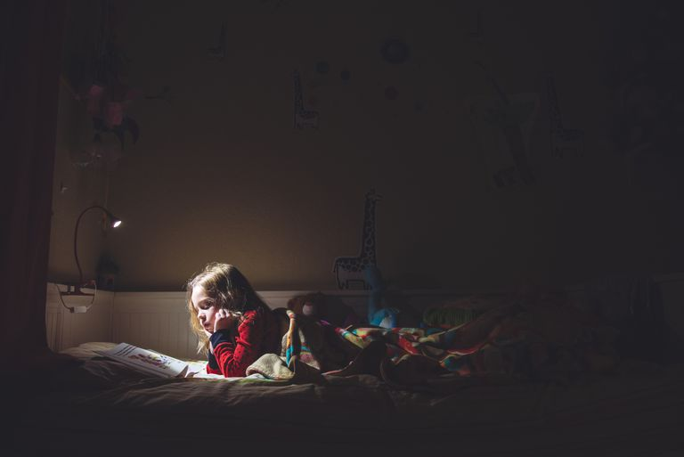 Girl reading in bed at night
