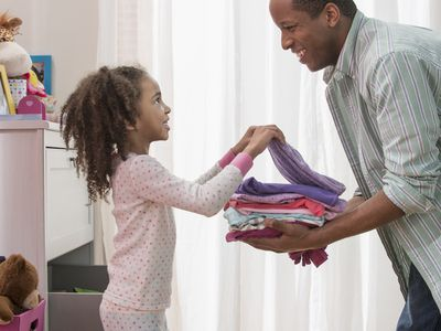 Father and daughter putting away folded clothes