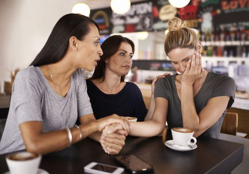 friends comforting upset woman at coffee shop
