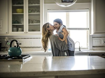 Mother kissing daughter (7yrs) in kitchen