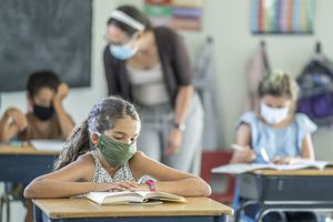Little girl wearing a mask at her desk in school