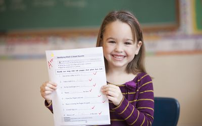 A smiling little girl holding a paper graded with an A++