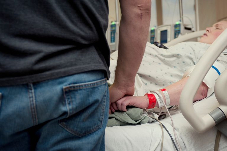 Man holding a laboring woman's hand in the hospital