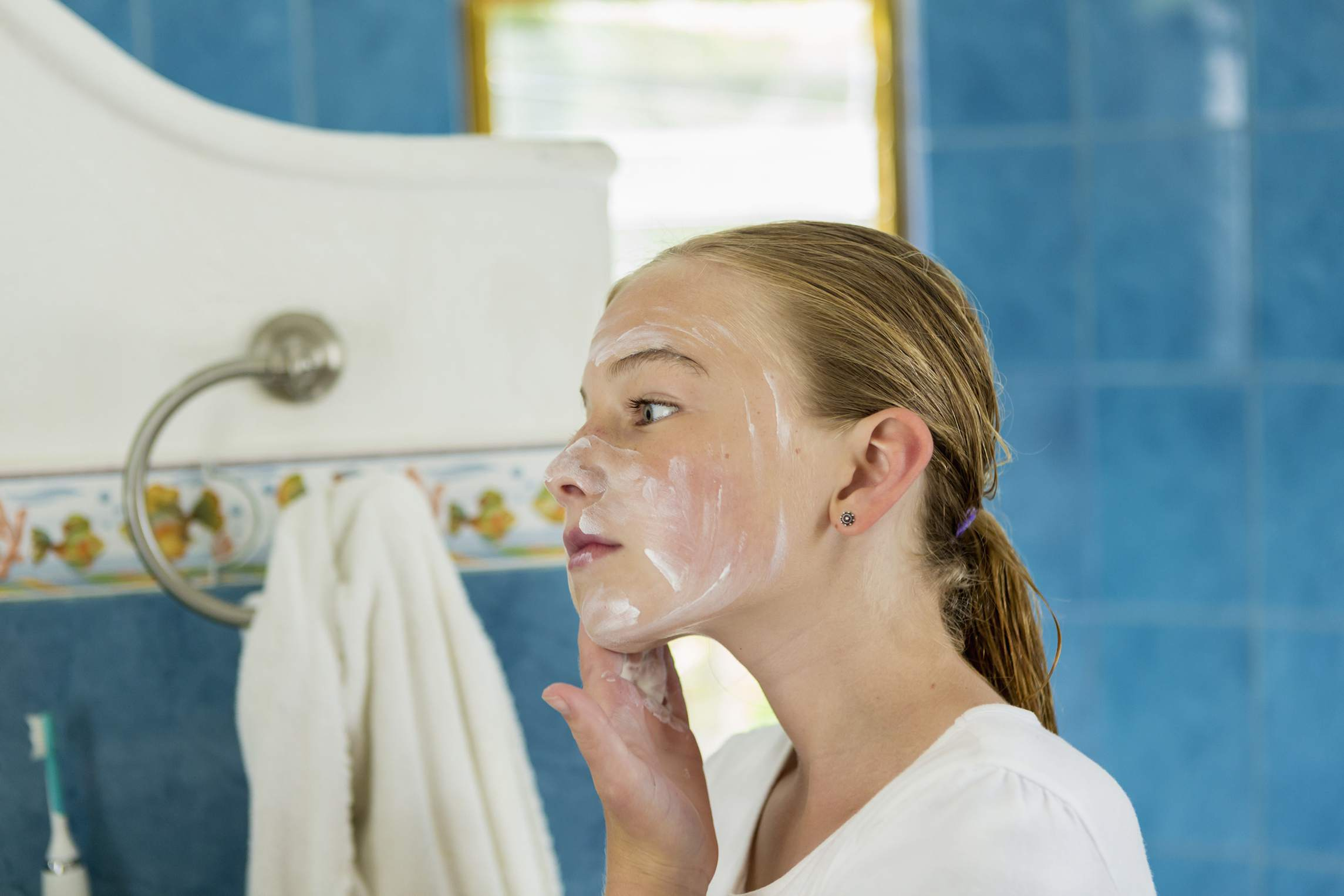 girl washing face with soap