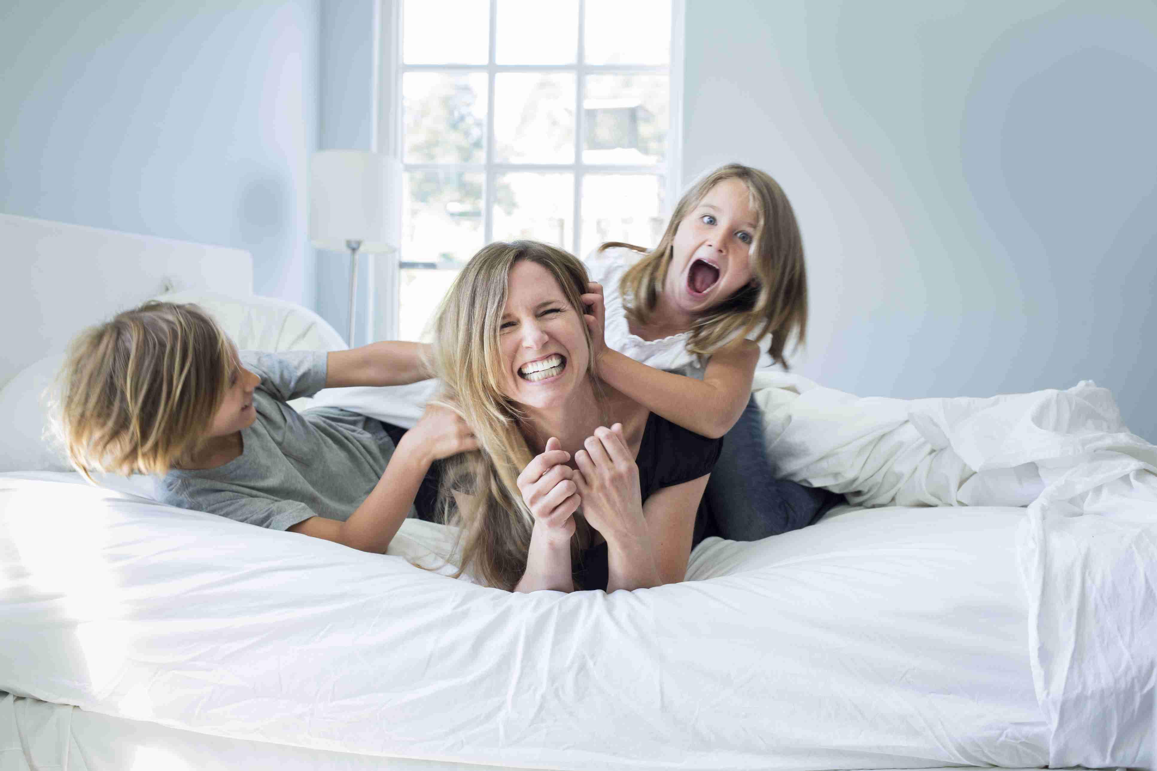 mom and kids laughing on bed