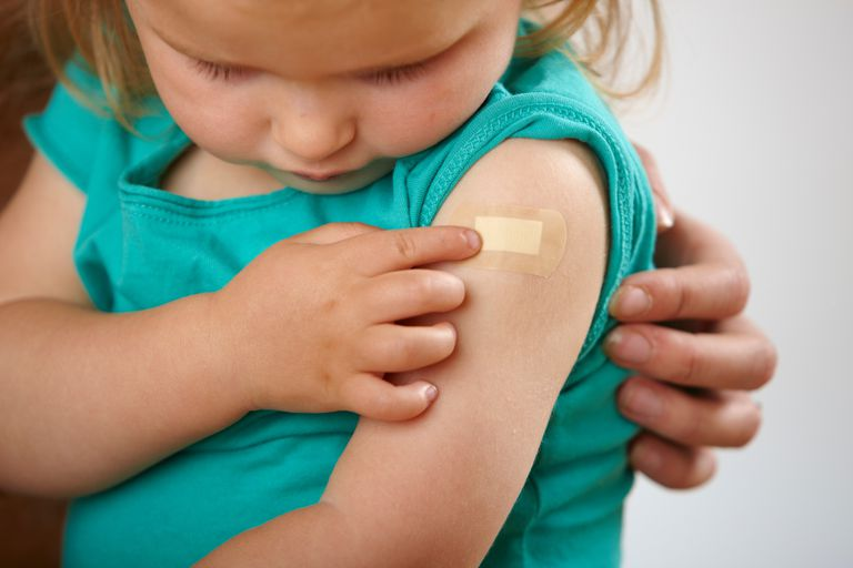Little girl looking at bandaid on upper arm