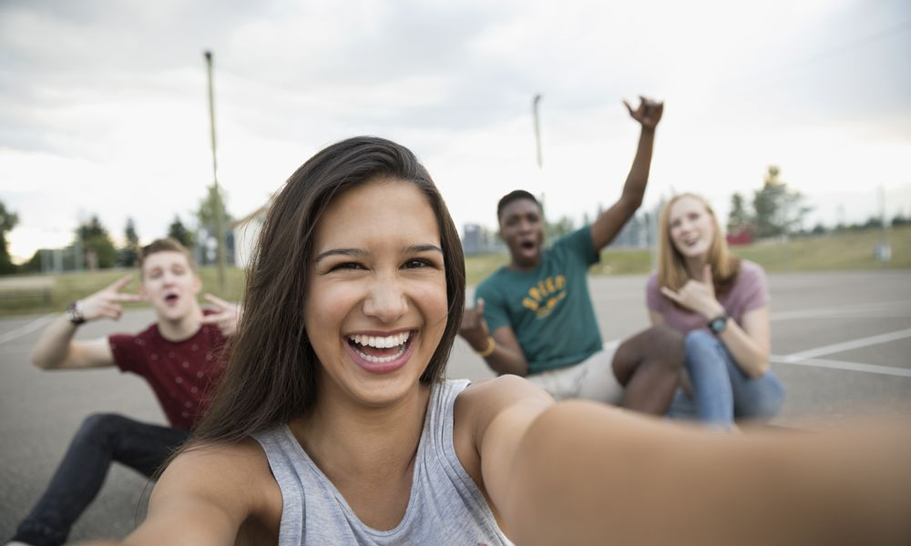 Portrait smiling teenage girl with friends taking selfie on outdoor basketball court