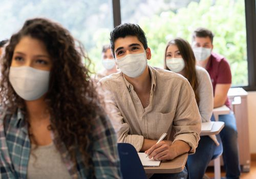 people in classroom wearing masks