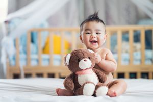 baby holding teddy bear