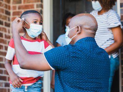 Father helps son put on face mask