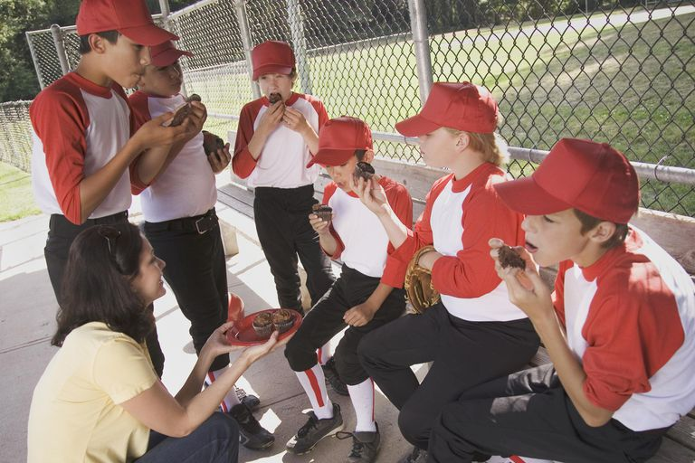 Mother giving cupcakes to boys (9-12) in baseball dugout