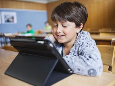 Happy schoolboy looking at digital tablet in classroom