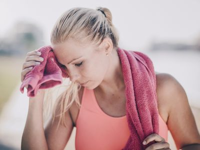 Woman wiping sweat with a towel