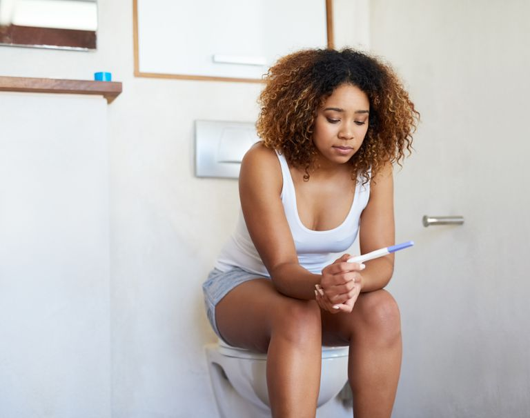 Woman in bathroom looking at pregnancy test