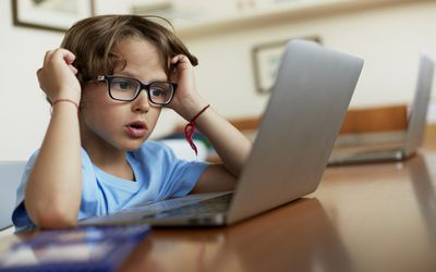 Boy wearing glasses stares at a laptop