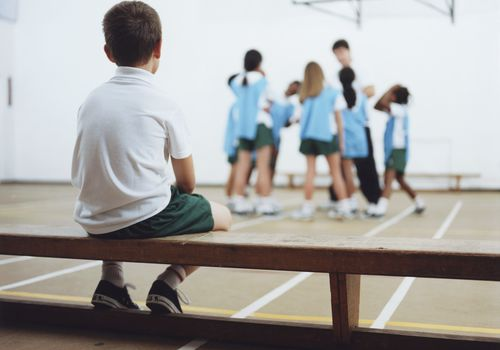Kids in gym class, and one boy sitting on a bench watching