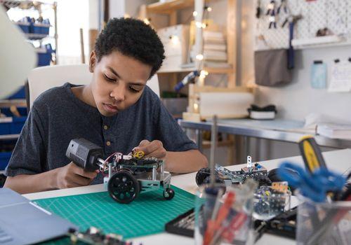 Teen boy solders wires to build robot