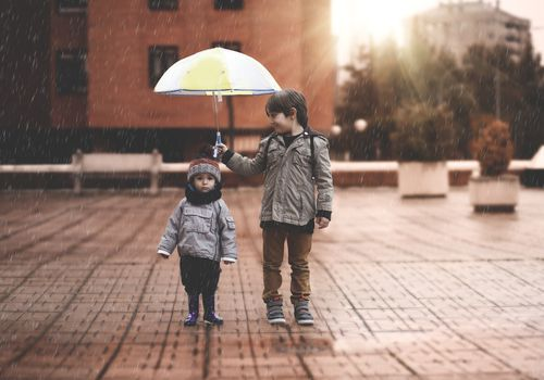 A little boy and his older brother protect themselves from the rain with an umbrella, in the city