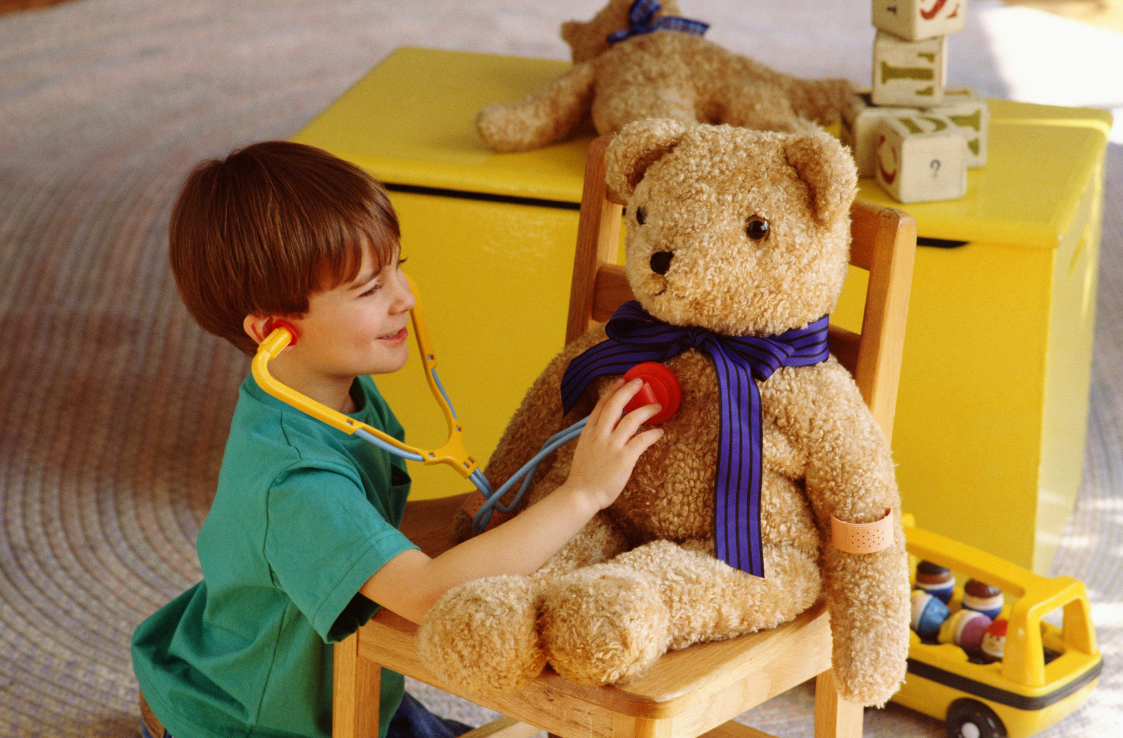 pretend play ideas - boy playing doctor with toy bear and stethoscope
