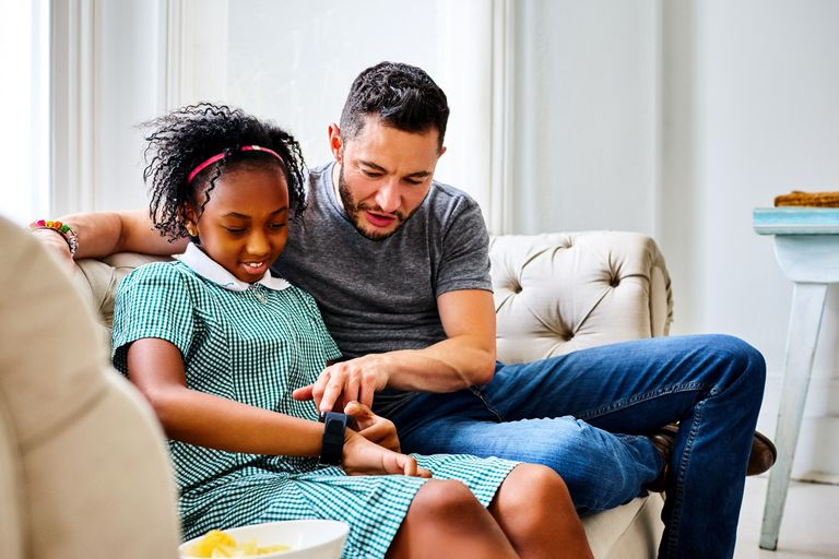 Father and daughter using smartwatch