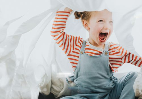 Young girl playing under a white sheet