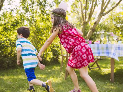 Boy and girl playing tag in garden