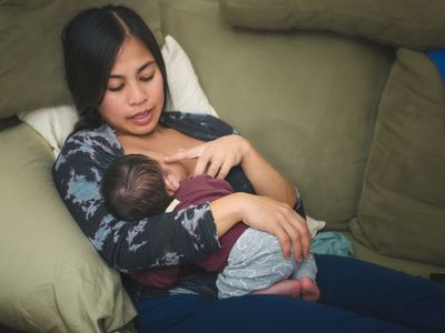 Woman nursing baby on couch