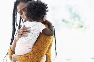 Woman holding and comforting baby daughter